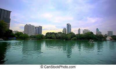 Cityscape view through the Serpentine lake in Park, Bangkok, Thailand