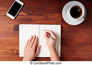 Woman hand writing in a diary, top view