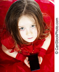 Cute little girl dressed in ball gown playing with...