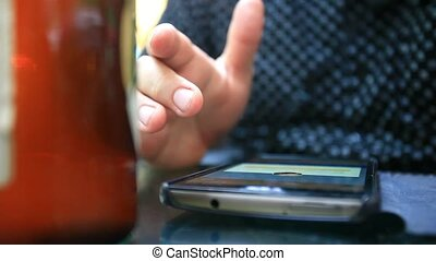 Close up of man texting on smartphone, drinking beer in...