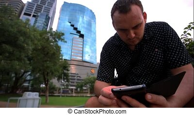 Young businessman using mobile phone in the big city. HD....