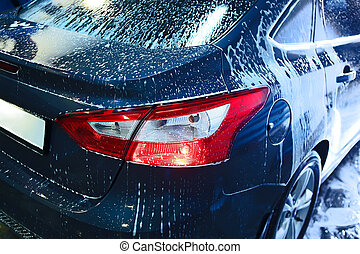 car covered with foam on car wash - blue car covered with...