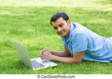 Surfing the web - Closeup portrait, young brown man in blue...