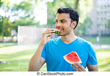 Tasty fruits - Closeup portrait, guy in blue shirt chowing...
