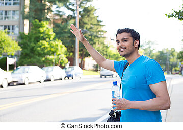 Hitchhiking or waving - Closeup portrait, young man in blue...