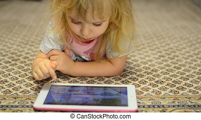 Cute Little Girl Works on Tablet Computer Lying on Carpet -...