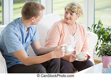Tea time - Young handsome male nurse and senior woman during...
