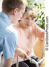 Helpful male nurse and older disabled woman