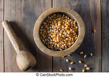 Wooden bowl full of popping corn kernals - Bowl filled with...