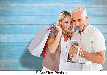 Composite image of happy couple with shopping bags and...