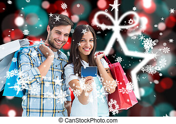 Composite image of couple with shopping bags and credit card...