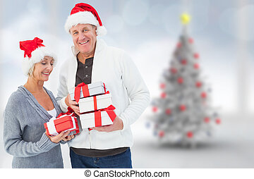 Composite image of festive mature couple holding christmas...