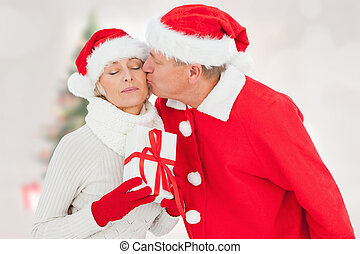 Composite image of festive mature couple holding gift -...