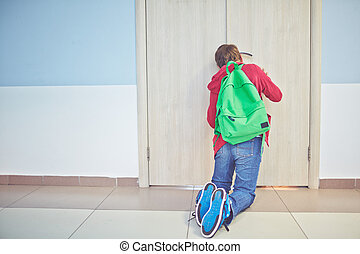 Peeping - Pre-teen schoolboy with backpack peeping into...