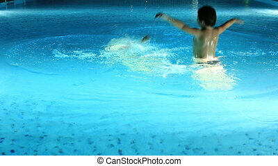 playing in swimming pool - young mother and son playing...