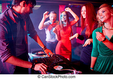 Deejay and pretty dancers - Male deejay adjusting sound with...