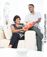 Mature Indian woman receiving a gift from her son