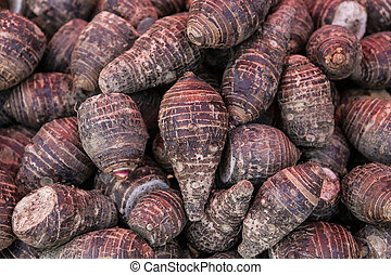 pile of taro for retail sale in local market. background of...