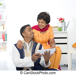 Mature 50s Indian woman and son using digital computer tablet at