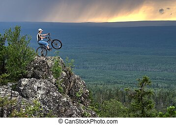 Biker with mountain bicycle stands on peak - Biker with...