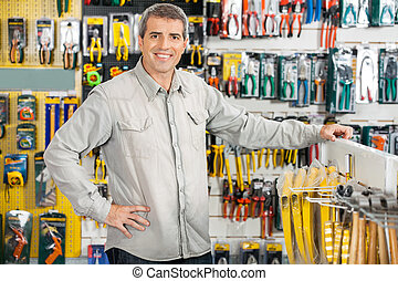 Happy Man Standing In Hardware Store - Portrait of happy...