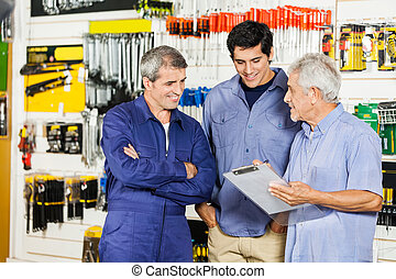 Worker Looking At Customers With Clipboard In Hardware Shop...