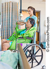 Nurse Removing Straps From Hydraulic Lift With Patient On...
