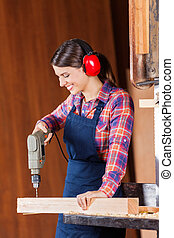 Female Carpenter Drilling Wood In Bandsaw - Young female...