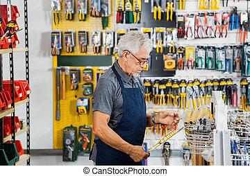 Man Working In Hardware Shop - Side view of senior man...