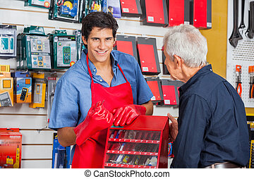 Salesman Showing Drill Bit To Man In Store - Portrait of...