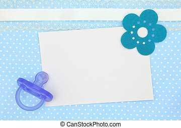 Blank card and blue pacifier on decorative polka dots background