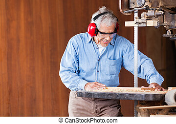 Carpenter Cutting Wood With Bandsaw - Senior carpenter...