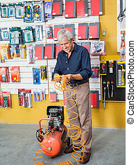 Senior Man Examining Air Compressor In Store - Full length...