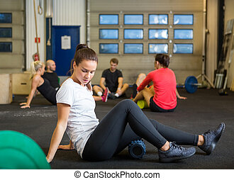 Woman Doing Relaxation Exercise In Crossfit Gym - Full...