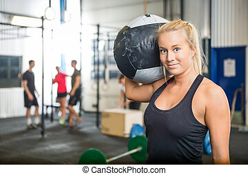 Woman Carrying Medicine Ball At Crossfit Gym - Portrait of...
