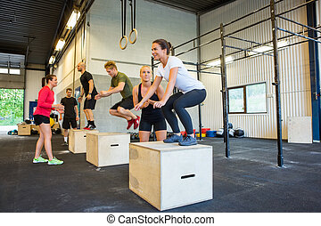 Athletes Doing Box Jumps At Gym - Male and female athletes...
