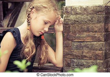 Portrait of sad blond teen girl sitting on the stairs at the...