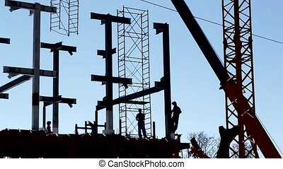 Builders Sihouettes on Site - The sihouettes of workers on...