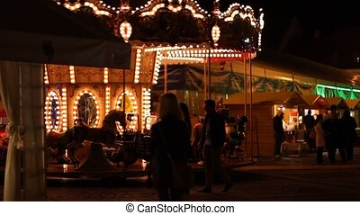 Carousel at Nightv - Spinning carousel at an amusement park,...
