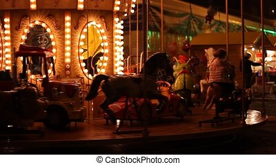 Carousel by Night - Spinning carousel at an amusement park,...