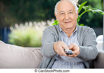 Elderly Man Using Remote Control While Sitting On Couch