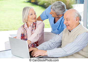 Caretaker Looking At Senior Woman By Man Using Laptop - Male...