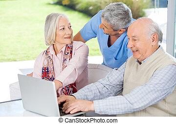 Caretaker Looking At Senior Woman By Man Using Laptop