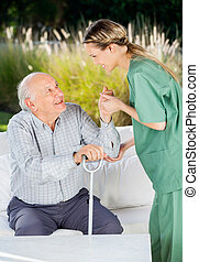 Female Nurse Helping Senior Man To Get Up From Couch - Side...