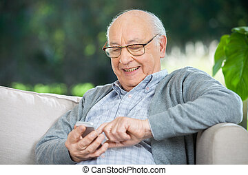 Smiling Senior Man Text Messaging Through Mobilephone -...