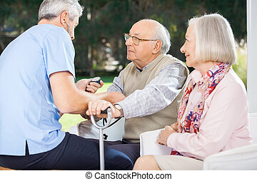 Male Doctor Measuring Blood Pressure Of Senior Man - Male...