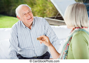 Senior Couple Talking While Playing Dominoes - Senior couple...