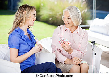 Happy Granddaughter Showing Playing Cards To Grandmother -...