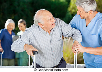 Male And Female Nurses Helping Senior People - Male and...