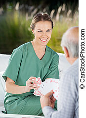Beautiful Female Nurse Playing Cards With Senior Man -...